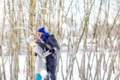 Ευτυχές νέο ζεύγος στο Winter Park που γελά και που έχει τη διασκέδαση οικογένεια υπαίθρια στοκ εικόνα
