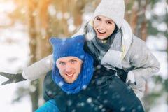 Ευτυχές νέο ζεύγος στο Winter Park που γελά και που έχει τη διασκέδαση οικογένεια υπαίθρια στοκ φωτογραφία