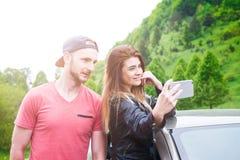Ευτυχές νέο ζεύγος, φίλοι που κάνει selfie καθμένος στο αυτοκίνητο νεολαίες ενηλίκων Καυκάσιοι άνθρωποι γη έννοιας ανασκόπησης πέ Στοκ Εικόνες