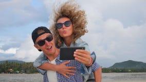 Ευτυχές νέο ζεύγος Hipser ερωτευμένο κάνοντας Piggyback Selfie στην παραλία Κορίτσι που έχει τη διασκέδαση στους φίλους πίσω Ταϊλ απόθεμα βίντεο