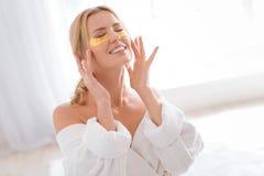 Ευτυχές νέο θηλυκό να κάνει μασάζ προσώπου Στοκ φωτογραφία με δικαίωμα ελεύθερης χρήσης