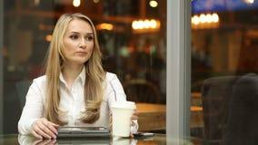 Ευτυχές νέο καφές ή τσάι κατανάλωσης γυναικών και χρησιμοποίηση του υπολογιστή ταμπλετών σε μια καφετερία επιχειρηματίας σε ένα ε απόθεμα βίντεο
