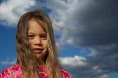 Ευτυχές νέο κορίτσι ενάντια στο νεφελώδη ουρανό στοκ εικόνες