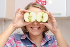 Ευτυχές νέο κορίτσι με δύο μήλα κοντά στα μάτια της στοκ εικόνα