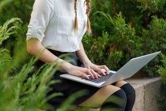 Ευτυχές νέο κορίτσι που εργάζεται στο lap-top στο πάρκο Στοκ εικόνες με δικαίωμα ελεύθερης χρήσης