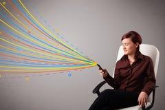 Ευτυχές κορίτσι που κρατά ένα τηλέφωνο με τις ζωηρόχρωμες αφηρημένες γραμμές Στοκ Φωτογραφία
