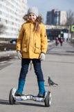 Ευτυχές νέο κορίτσι που οδηγεί το μόνο ισορροπημένο όχημα στη διάβαση οδών στοκ φωτογραφία με δικαίωμα ελεύθερης χρήσης