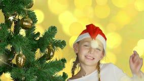 Ευτυχές νέο κορίτσι που χορεύει κοντά στο χριστουγεννιάτικο δέντρο στο κόκκινο καπέλο Santa Ευτυχής νέος καυκάσιος στενός επάνω π απόθεμα βίντεο