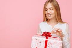 Ευτυχές νέο κορίτσι, σε ένα άσπρο φόρεμα, με ένα κιβώτιο δώρων υπό εξέταση, στο δέο του δώρου, σε ένα ρόδινο υπόβαθρο στοκ φωτογραφίες με δικαίωμα ελεύθερης χρήσης