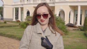 Ευτυχές νέο κορίτσι στα συμπαθητικά ενδύματα που περπατά γύρω από το λιμένα απόθεμα βίντεο