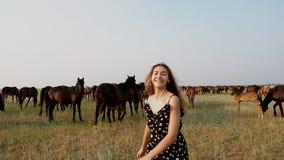 Ευτυχές νέο κορίτσι στον τομέα με τη βοσκή του κοπαδιού αλόγων στο καλοκαίρι απόθεμα βίντεο