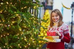 Ευτυχές νέο κορίτσι στο πουλόβερ διακοπών με το σωρό των χριστουγεννιάτικων δώρων στοκ εικόνες