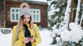 Ευτυχές νέο κορίτσι χρησιμοποιώντας app στο smartphone, χαμογελώντας και texting στο κινητό τηλέφωνο Γυναίκα που φορά ένα χειμερι απόθεμα βίντεο