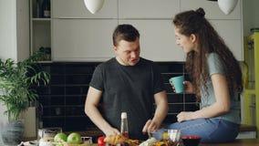 Ευτυχές νέο μυρμήγκι μαγειρέματος ζευγών που μιλά στην κουζίνα στο σπίτι Ελκυστικό άτομο που ταΐζει τη φίλη του κόβοντας απόθεμα βίντεο