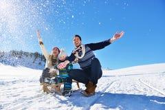 Ευτυχές νέο οικογενειακό παιχνίδι στο φρέσκο χιόνι στην όμορφη ηλιόλουστη χειμερινή ημέρα υπαίθρια στη φύση Στοκ Εικόνα
