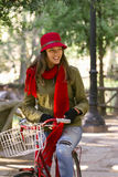 Ευτυχές νέο οδηγώντας ποδήλατο γυναικών την ημέρα φθινοπώρου στοκ εικόνες