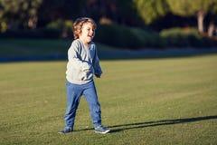 Ευτυχές νέο παιχνίδι αγοριών με την κόκκινη σφαίρα στην πράσινη χλόη στοκ εικόνα