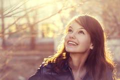 Ευτυχές νέο πορτρέτο πόλεων φωτός του ήλιου γυναικών χαμόγελου