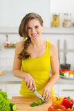 Ευτυχές νέο τέμνον αγγούρι γυναικών στην κουζίνα Στοκ εικόνες με δικαίωμα ελεύθερης χρήσης