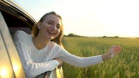 Ευτυχές νέο ταξίδι που χαμογελά την όμορφη νέα γυναίκα που απολαμβάνει το οδικό ταξίδι στον τομέα σίτου θερινής φύσης Ο βραχίονας απόθεμα βίντεο