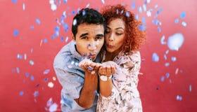 Ευτυχές νέο φυσώντας κομφετί ζευγών στον εορτασμό της αγάπης τους Στοκ Εικόνα