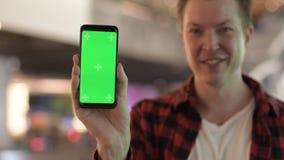 Ευτυχές νέο όμορφο άτομο που παρουσιάζει τηλέφωνο στην πόλη τη νύχτα απόθεμα βίντεο