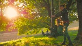 Ευτυχές νέο mom με ένα μικρό κορίτσι που ταλαντεύεται στο πάρκο μαζί στο ηλιοβασίλεμα Μητέρα και κόρη που οδηγούν στην ταλάντευση φιλμ μικρού μήκους