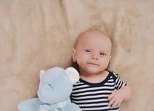 Ευτυχές νεογέννητο αγόρι με το παιχνίδι που φορά στο γδυμένο ιματισμό Στοκ Φωτογραφία