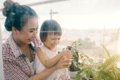 Ευτυχές νερό κορών μητέρων και παιδιών στο μικρό κήπο Στοκ εικόνα με δικαίωμα ελεύθερης χρήσης