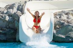 Ευτυχές ξανθό κορίτσι που γλιστρά μέσα το aquapark Στοκ Εικόνες