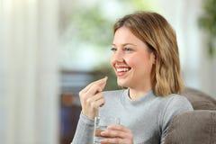 Ευτυχές ξανθό κορίτσι που παίρνει ένα χάπι βιταμινών στο σπίτι Στοκ φωτογραφίες με δικαίωμα ελεύθερης χρήσης