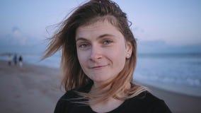 Ευτυχές ξανθό κορίτσι στην παραλία στο χρόνο ηλιοβασιλέματος ή λυκόφατος απόθεμα βίντεο