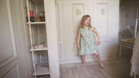 Ευτυχές ξανθό κορίτσι στο φόρεμα που έχει τη διασκέδαση που χορεύει στο εσωτερικό σε ένα ηλιόλουστο άσπρο δωμάτιο στο σπίτι ή τον απόθεμα βίντεο