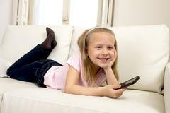 Ευτυχές ξανθό μικρό κορίτσι στον εγχώριο καναπέ που χρησιμοποιεί Διαδίκτυο app στο κινητό τηλέφωνο Στοκ φωτογραφία με δικαίωμα ελεύθερης χρήσης