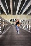Ευτυχές οδηγώντας ποδήλατο γυναικών με το καλάθι πέρα από τη γέφυρα πόλεων στοκ εικόνες