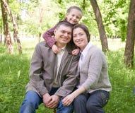 Ευτυχές οικογένεια και παιδί στο θερινό πάρκο, όμορφο τοπίο με τα δέντρα και πράσινη χλόη Στοκ φωτογραφία με δικαίωμα ελεύθερης χρήσης