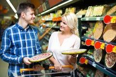 Ευτυχές οικογενειακό ζεύγος που επιλέγει την κατεψυγμένη πίτσα Στοκ Εικόνες