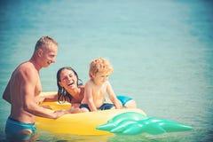 Ευτυχές οικογενειακό ζεύγος στην καραϊβική θάλασσα Ανανάς διογκώσιμος ή στρώμα αέρα Χαρά δραστηριότητας παραλιών των Μαλδίβες ή τ στοκ φωτογραφία