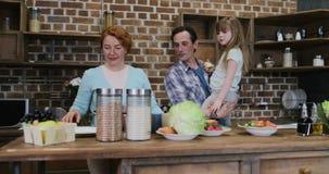 Ευτυχές οικογενειακό μαγείρεμα μαζί στην κουζίνα, γονείς με το μικρούς γιο και την κόρη που προετοιμάζουν τα τρόφιμα μαζί στο σπί απόθεμα βίντεο