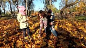 Ευτυχές οικογενειακό παιχνίδι ανθρώπων με τα ζωηρόχρωμα φύλλα φθινοπώρου φιλμ μικρού μήκους