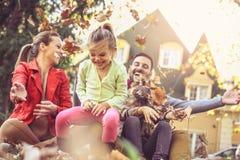 Ευτυχές οικογενειακό παιχνίδι με τα φύλλα στο κατώφλι στοκ εικόνα