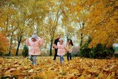 Ευτυχές οικογενειακό παιχνίδι στο πάρκο φθινοπώρου Στοκ Φωτογραφία