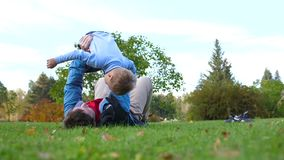 Ευτυχές οικογενειακό παιχνίδι στο χορτοτάπητα Ένας νέος αγαπώντας πατέρας ανέθρεψε το παιδί υψηλό επάνω από το κεφάλι του, τα χαμ φιλμ μικρού μήκους