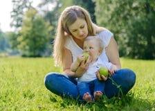 Ευτυχές οικογενειακό στη χλόη στο πάρκο Στοκ Φωτογραφία
