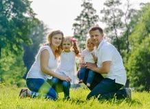 Ευτυχές οικογενειακό στη χλόη στο πάρκο Στοκ φωτογραφία με δικαίωμα ελεύθερης χρήσης
