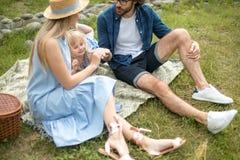 Ευτυχές οικογενειακό υπαίθρια με τη χαριτωμένη κόρη τους, μπλε ενδύματα, γυναίκα στο καπέλο στοκ εικόνες με δικαίωμα ελεύθερης χρήσης