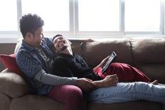 Ευτυχές ομοφυλοφιλικό ζεύγος που εξετάζει τις εικόνες στην ταμπλέτα στοκ φωτογραφία με δικαίωμα ελεύθερης χρήσης