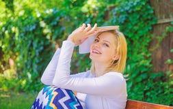 Ευτυχές ονειροπόλο διαβασμένο βιβλίο γυναικείων όμορφο βιβλιοψειρών υπαίθρια ηλιόλουστη ημέρα Το κορίτσι κάθεται τη χαλάρωση πάγκ στοκ φωτογραφία με δικαίωμα ελεύθερης χρήσης