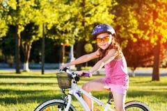 Ευτυχές οδηγώντας ποδήλατο κοριτσιών παιδιών στο θερινό ηλιοβασίλεμα Στοκ φωτογραφία με δικαίωμα ελεύθερης χρήσης