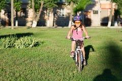 Ευτυχές οδηγώντας ποδήλατο κοριτσιών παιδιών στο θερινό ηλιοβασίλεμα Στοκ Φωτογραφία